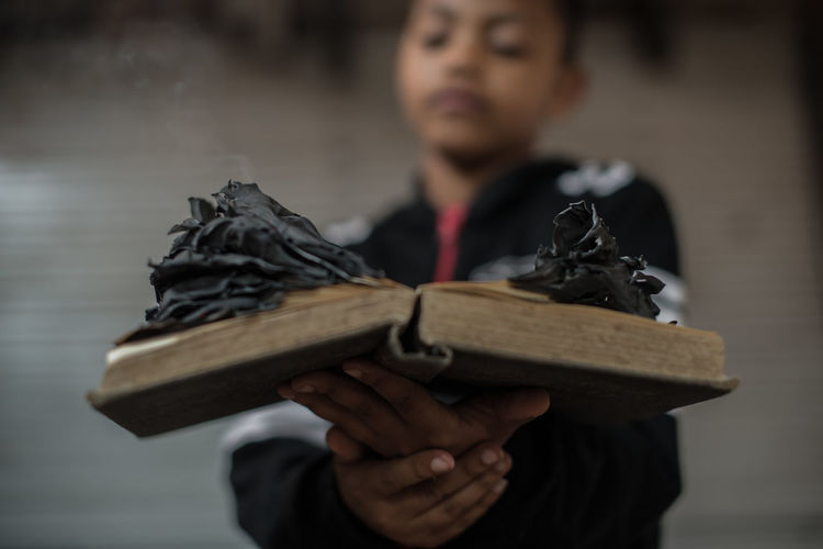 Boy holding burnt book