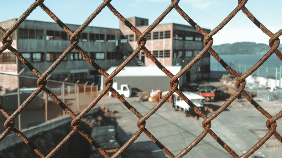 Close-up of chainlink fence against building in city