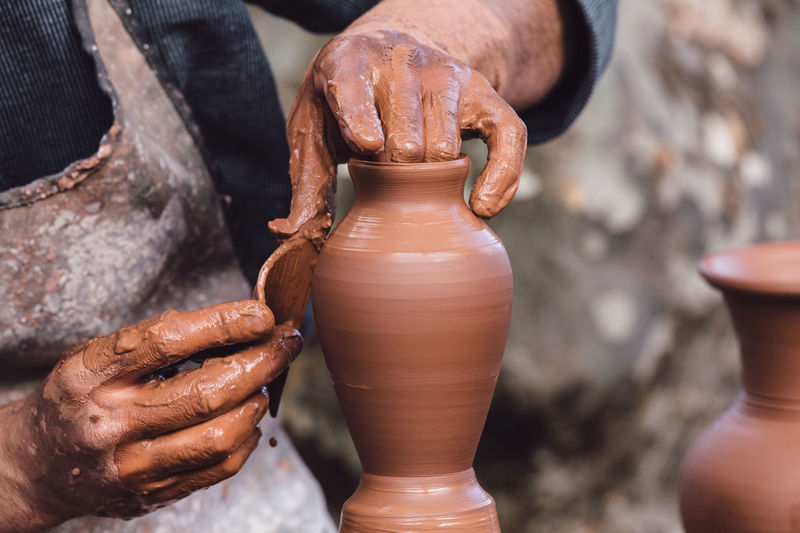 Cropped Image Of Craftsperson Shaping Urn