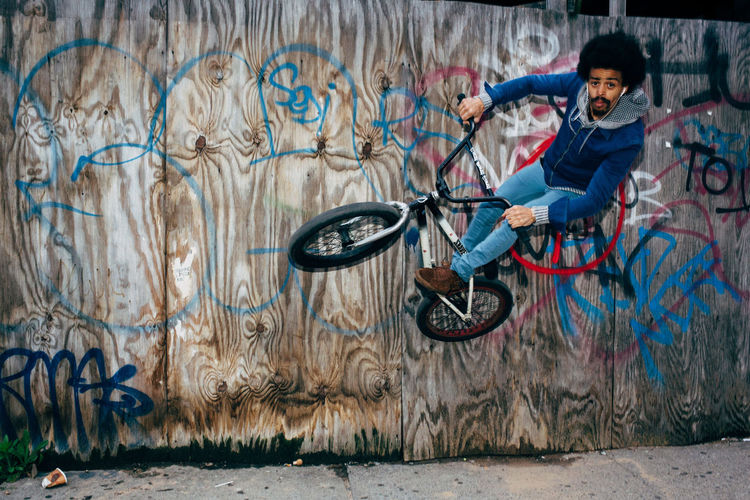 Portrait of teenage boy on bicycle in city
