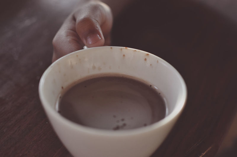 Close-up of hand holding cup of coffee