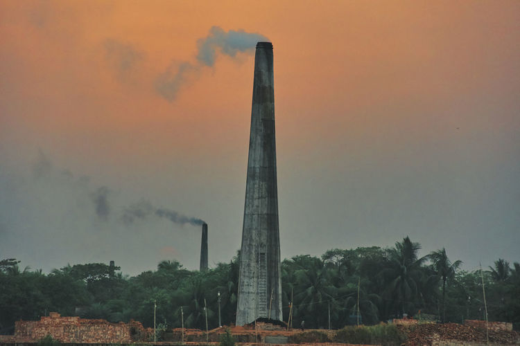 Panoramic view of factory against sky during sunset