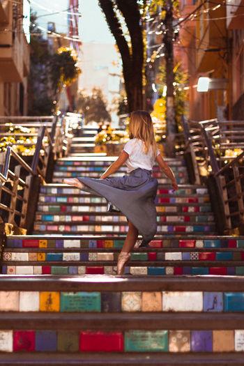 Beautiful female fashion dancer in urban sunny setting