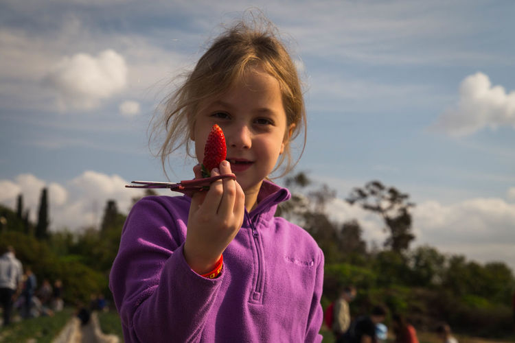Portrait of cute smiling girl holding strawberry and scissors at farm