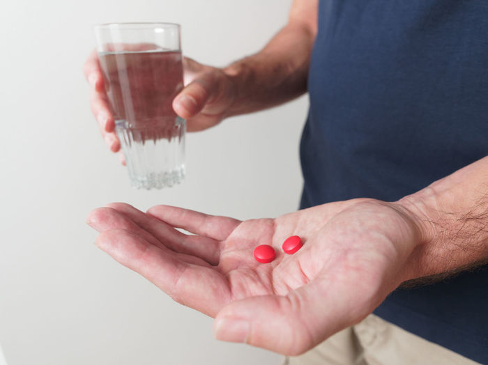 Midsection of man holding drinking glass with water and pills standing against wall
