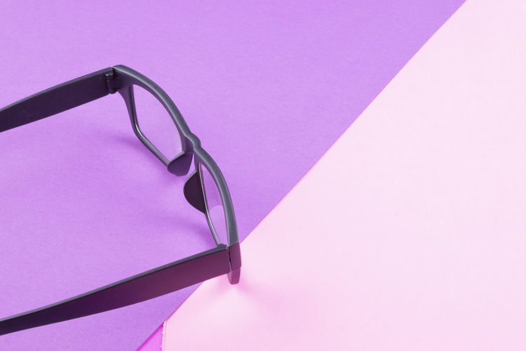 eye glasses spectacles with shiny black frame on pastel color background Pink Color No People Copy Space Indoors  Close-up Still Life Glasses Single Object Studio Shot Purple High Angle View Paper Fashion Colored Background Eyeglasses  Blue Simplicity Wall - Building Feature Relaxation Table Personal Accessory