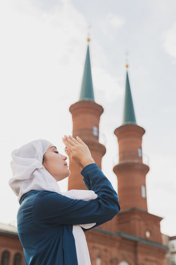 Low angle view of woman worshiping outdoors