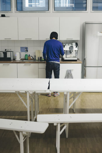 Man preparing coffee in office canteen