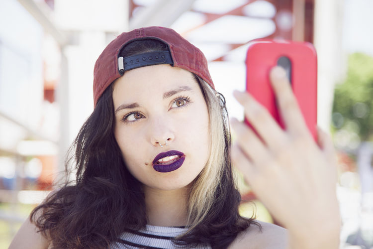 Close-Up Portrait Of Young Woman Taking Selfie With Phone