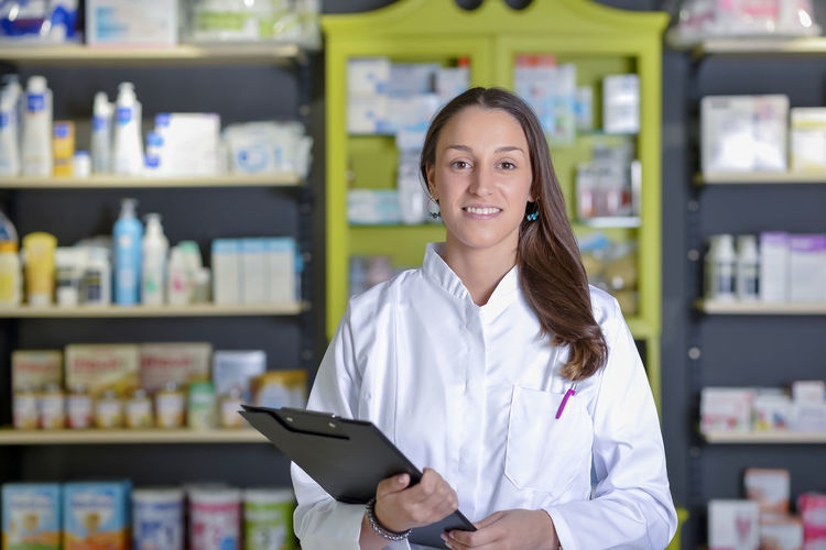 Portrait Of Female Pharmacist With Clipboard Standing Against Shelf In Store