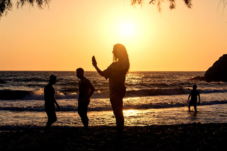 People playing, swimming in the waves in the island of Patmos, Greece in summer time Beach Beauty In Nature Group Of People Horizon Horizon Over Water Land Leisure Activity Lifestyles Men Nature Orange Color Outdoors Real People Scenics - Nature Sea Silhouette Sky Sunset Togetherness Water