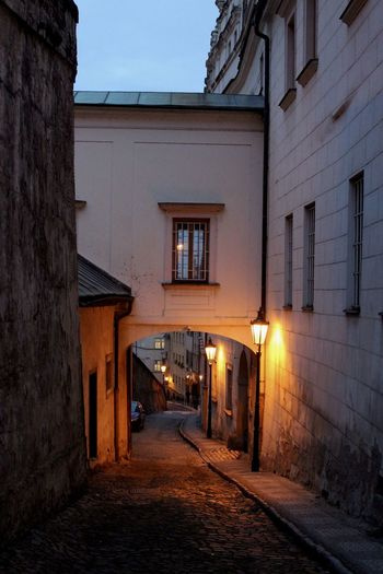 Empty alley amidst buildings in city at dusk