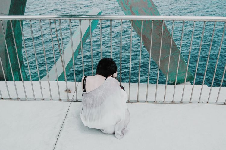 Rear view of woman on railing against sea