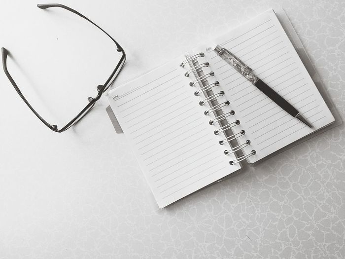 Directly above shot of pen and diary with eyeglasses on white table