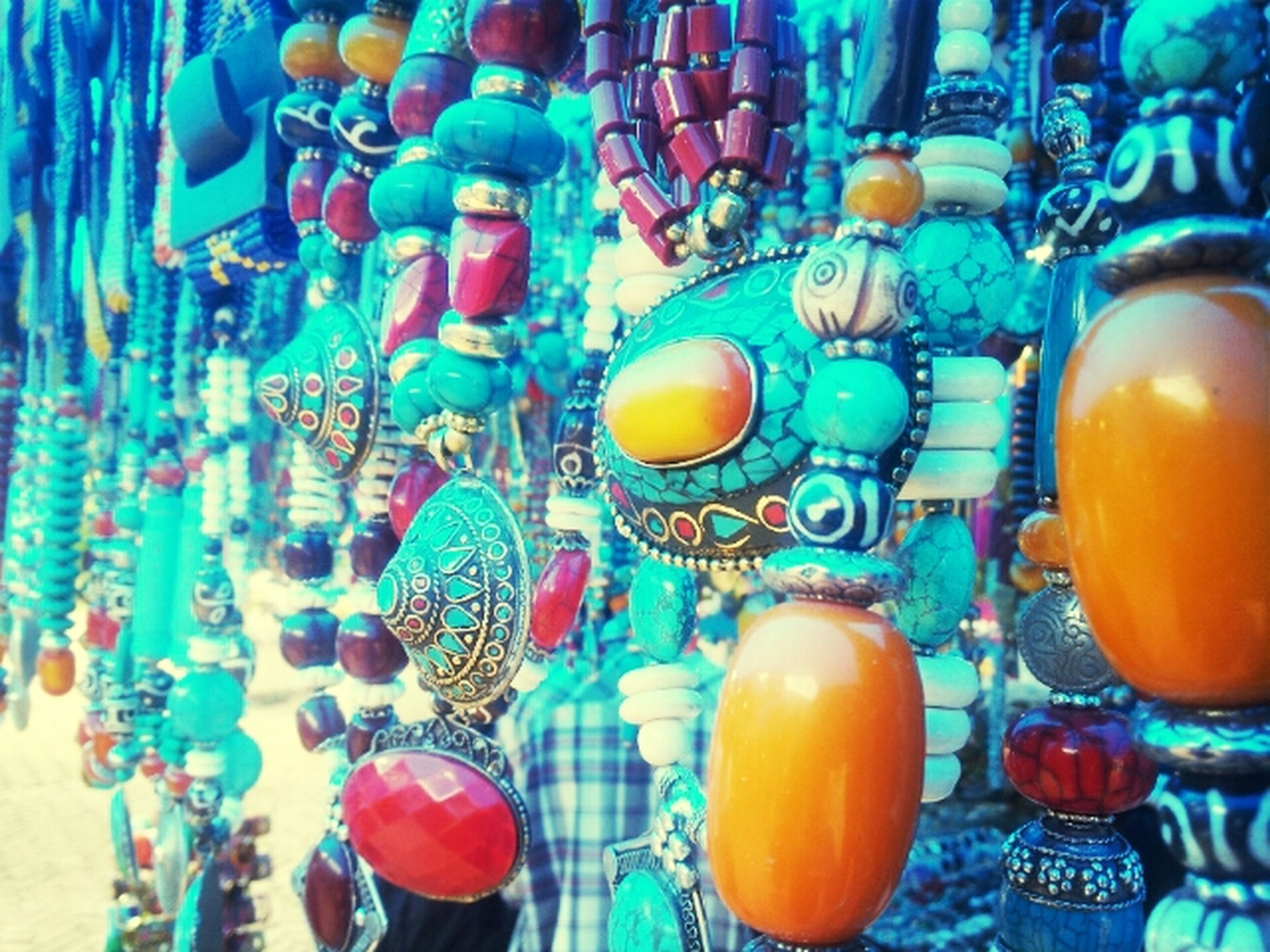 large group of objects, multi colored, variation, abundance, arrangement, indoors, still life, in a row, choice, side by side, order, collection, bottle, colorful, hanging, retail, group of objects, for sale, glass - material, blue