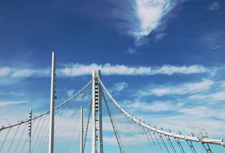 Low angle view of bay bridge with steel cables against sky