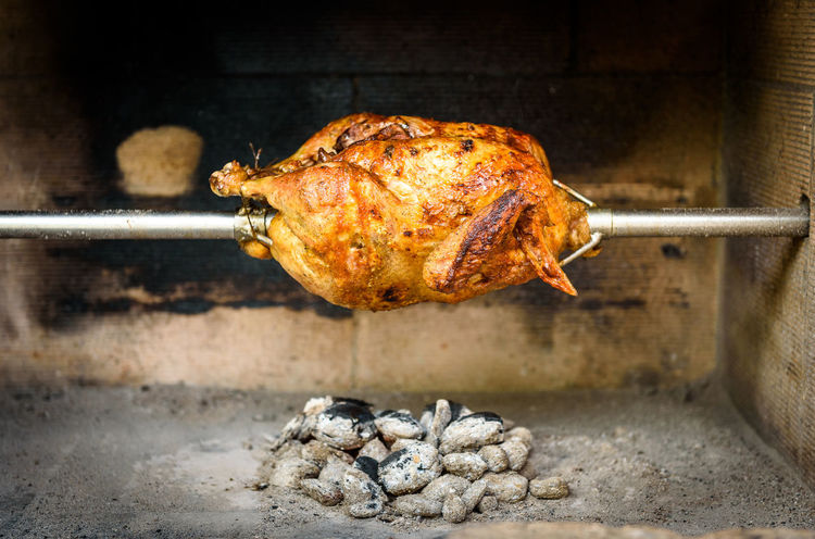 Cooking and preparing rotisserie chicken on the grill with Charcoal and Briquettes in the professional steak house or barbecue restaurant BBQ BBQ Time Cooking Meal Barbecue Barbecue Grill Charcoal Chicken Meat Coal Delicious Fire Food Fresh Grill Grilled Chicken Juicy Meat Outdoors Picnik Preparing Roast Chicken Roasted Rotisserie Rotisserie Chicken White Meat