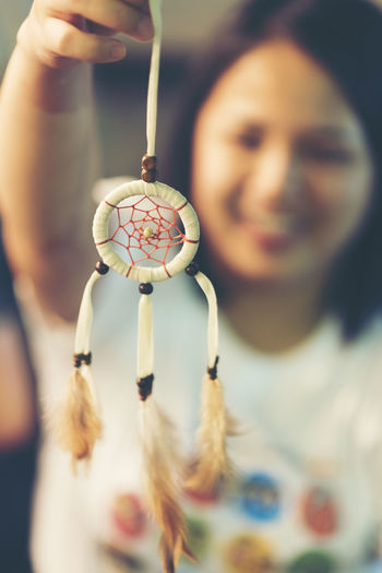 Close-Up Of Young Woman Holding Dreamcatcher