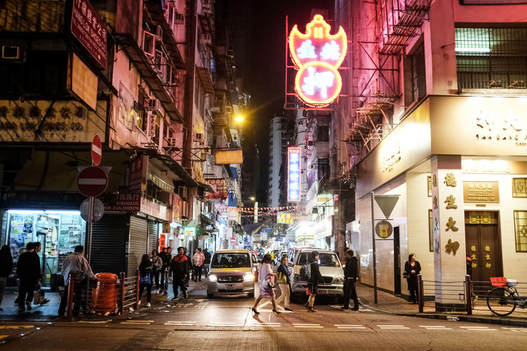 Hong Kong Streetlife Architecture Building Building Exterior Built Structure Car City City Life City Street Crowd Group Of People Illuminated Land Vehicle Mode Of Transportation Motion Motor Vehicle Neon Night Outdoors Real People Road Sign Street Transportation