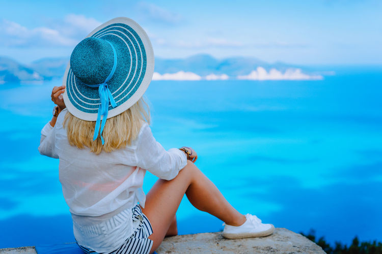 Attractive female tourist with turquoise sun hat enjoying amazing azure seascape, Greece. Cloudscape shadows on the sea surface in background Coastline Landscape Females Lady Mediterranean  Panorama Summertime Attitude Azure Blond Hair Blue Girl Greece Horizon Horizon Over Water Kefalonia Lifestyles Model Myrtos Beach Pattern Riviera Seaside Sunhat Vacation Viewpoint Women