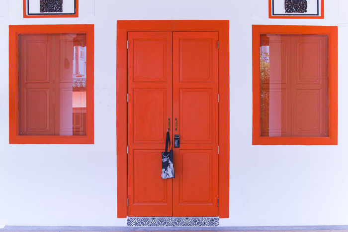 White wall with doors and windows in striking red of old-style residential building. Architecture Colors Doors Singapore Striking Colors Building Door Doorway Entrance Old Style Red Color Residential Building Simple Design Street White Color Windows