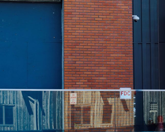 Maybe the architect should rethink use of glass around his new building? Reflection Architecture JGLowe Built Structure Architecture Building Exterior Wall - Building Feature Building Sign Brick No People Brick Wall Protection Day Wall Blue Door