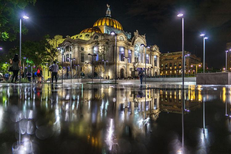 Illuminated palacio de bellas artes reflecting in puddle on street