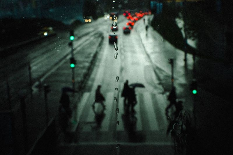 High Angle View Of Silhouette People Crossing Road Seen Through Wet Window At Night