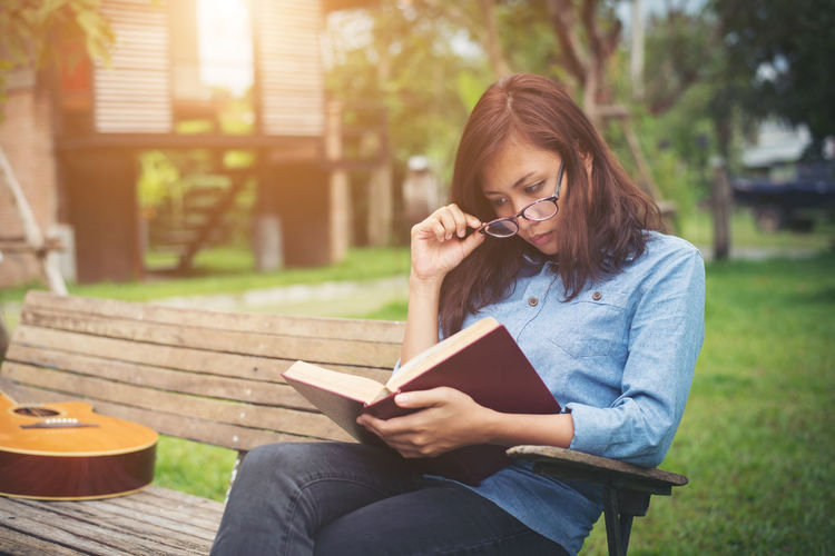 Young woman reading book while sitting on park bench