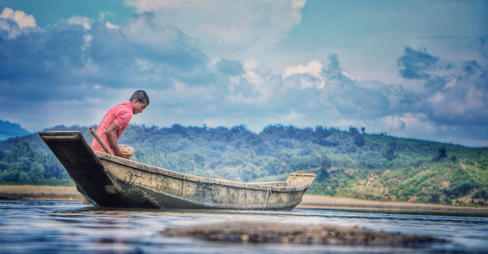 Side view of man sitting in boat on lake against sky