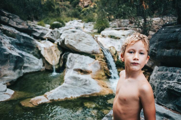 Portrait of shirtless boy on rock