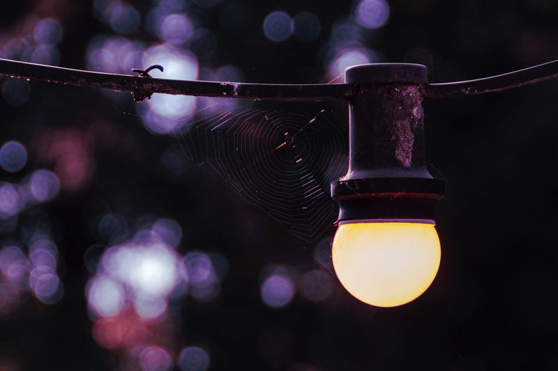 Low angle view of illuminated lighting equipment hanging at night