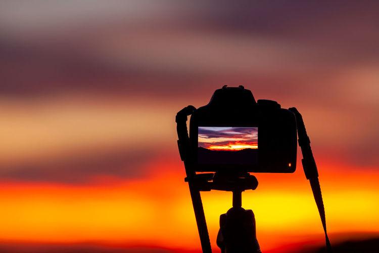 Silhouette of camera against orange sky