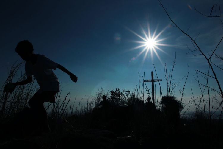 Silhouette man standing on field against bright sun