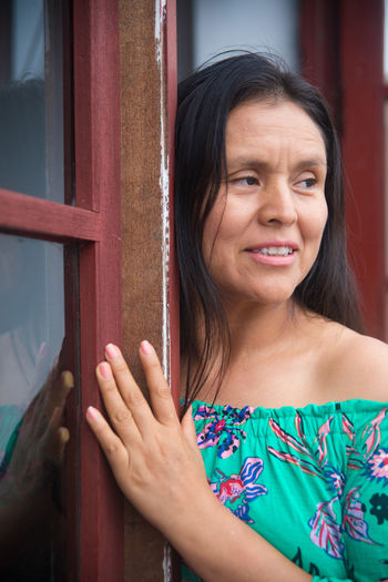 Portrait of a smiling young woman standing against window