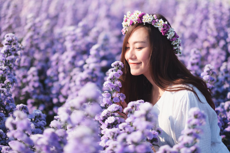 Portrait of smiling woman with purple flowers