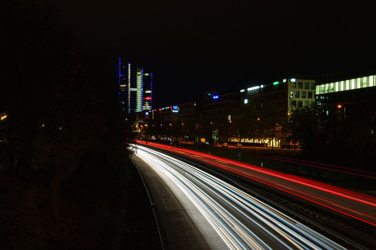 Light trails on street against illuminated buildings at night