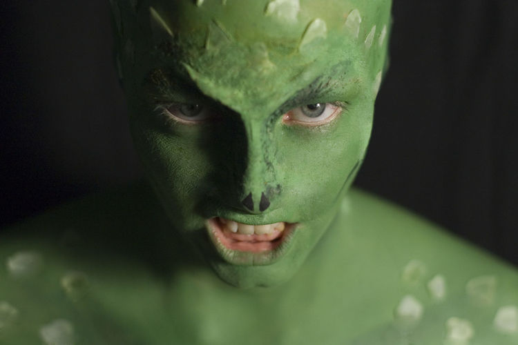 Close-up portrait of man with green body paint in darkroom