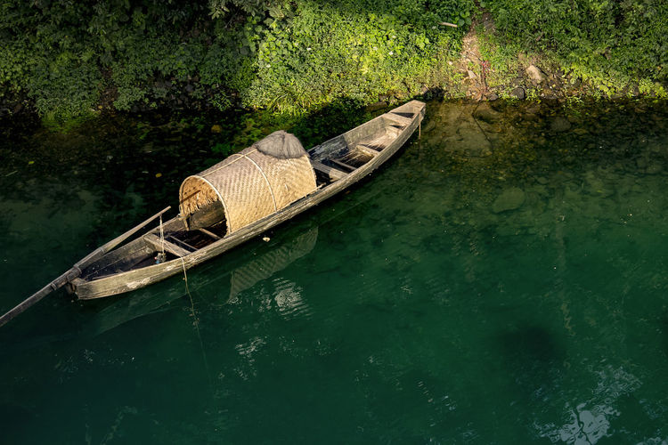 A fishing boat is docked at the river, Hunan province, China. Dongjiang Lake Hunan Beauty In Nature Boat Canal China Day Gondola - Traditional Boat Mode Of Transport Moored Nature Nautical Vessel No People Oar Outdoors Rowboat Transportation Water Waterfront