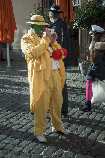 "Cologne, Germany - March 14th 2014: A man wears the costume from the movie ""The Mask"", a yellow suit with a yellow hat and green face Carnival Celebration Cologne Disguise Event Man Suit Taking Photos Alaaf Colorful Costume Dress Up Film Roll Full Length Green Face Green Make-up Joy Nonsense Outdoors Reveller Roleplay Street Street Carnival The Mask Yellow"