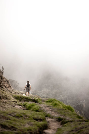 Rear View Of Woman Walking On Mountain During Foggy Weather
