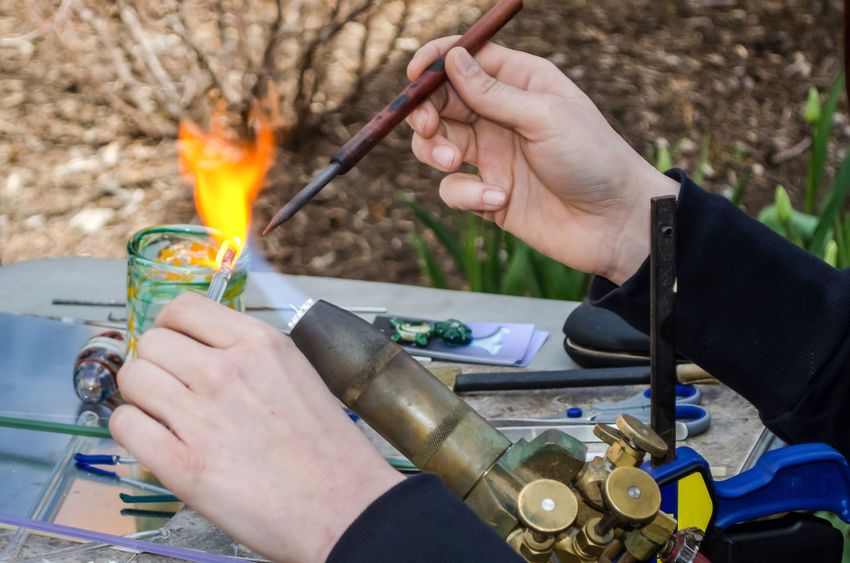 An artist works with glass, fire and a small torch, to create art Artist Glass Art Art And Craft Body Part Burning Craft Creating Finger Fire Fire - Natural Phenomenon Flame Hand Heat - Temperature Holding Human Body Part Human Hand Human Limb Melting Nature Occupation One Person Real People Skill  Table Unrecognizable Person