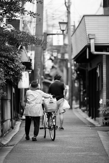 Building Exterior Architecture City Built Structure Rear View Real People Street Women Adult City Life Lifestyles Full Length Walking Transportation Day Men People Two People Senior Adult Bicycle