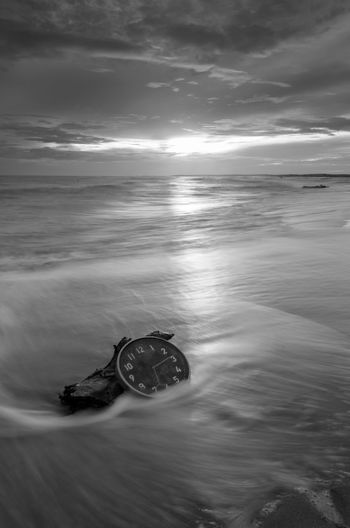Concept alarm clock on beach of island, malaysia. Fine art black and white. Blackandwhite Fine Art Photography Long Exposure Wallpaper Background Malaysia Concept Wall Clock Nautical Vessel Water Sea Beach Wave Sailing Ship Sunset Business Finance And Industry Harbor UnderSea Low Tide Seascape