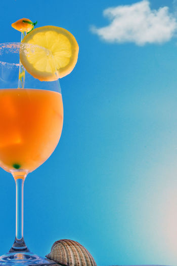 Close-up of oranges against blue sky. orange juice cocktail on the beach sand