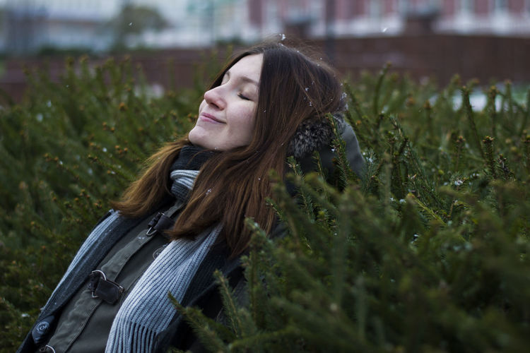 Smiling woman with closed eyes leaning on plants at park during winter