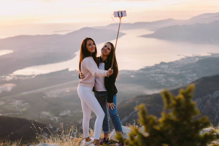 two girls travel in mountains and using phone for selfie photo Travel Vacations Beauty In Nature Camera - Photographic Equipment Friendship Happiness Leisure Activity Lifestyles Mobile Phone Mountain Nature Outdoors Photo Messaging Photographing Portable Information Device Real People Self Portrait Photography Selfie Smiling Togetherness Two People Wireless Technology Women Young Adult Young Women