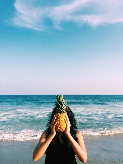 Woman Hiding Face With Pineapple At Beach
