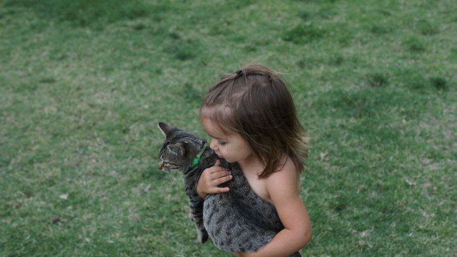 Girl Holding Cat Standing On Grass