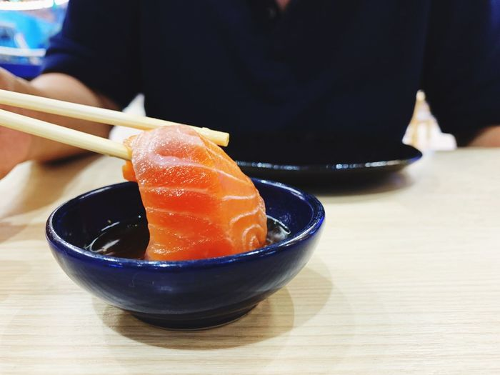 Dipping salmon sashimi in soy sauce. Soy Sauce Eating Sashimi  Salmon Food And Drink Table One Person Freshness Food Bowl Asian Food